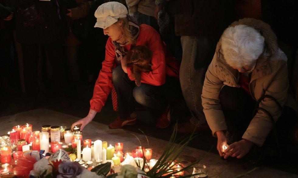 Dos mujeres encienden una vela en recuerdo de los estudiantes que fueron atacados por la policía en 1989