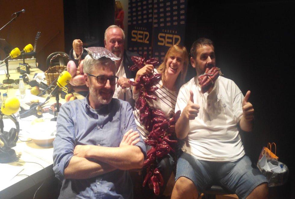 Mikel Iturriaga, David de Jorge y Gemma Nierga posan con los productos gastronómicos que les ha regalado Kepa Freire (al fondo) en el 'Hoy por Hoy' realizado en Bilbao con motivo del Foro de Empleo juvenil