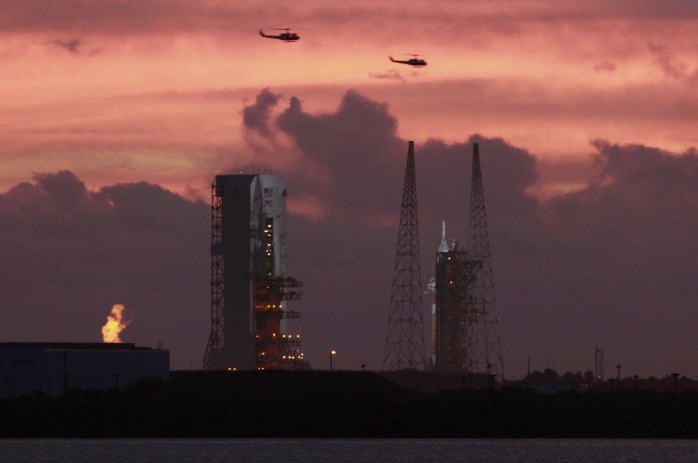 Dos helicópteros militares sobrevuelan la plataforma de lanzamiento de cohete Delta IV, en Cabo Cañaveral
