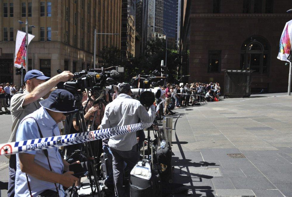 Medios de comunicación permanecen en las inmediaciones de la cafetería que un hombre armado tiene tomada desde primeras horas de la mañana en Sídney (Australia).