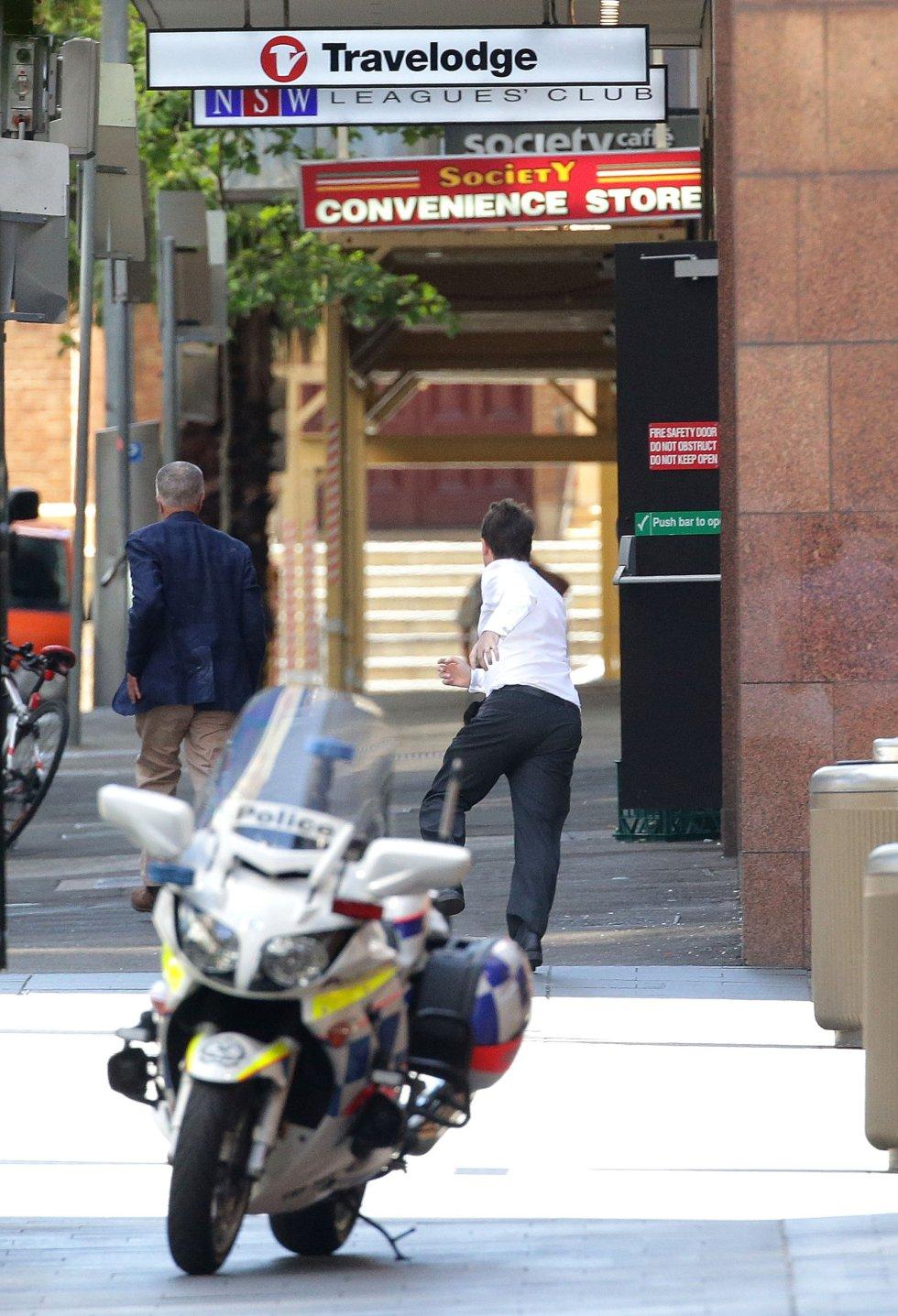 Dos rehenes salen corriendo del café tras lograr escapar del secuestrador.