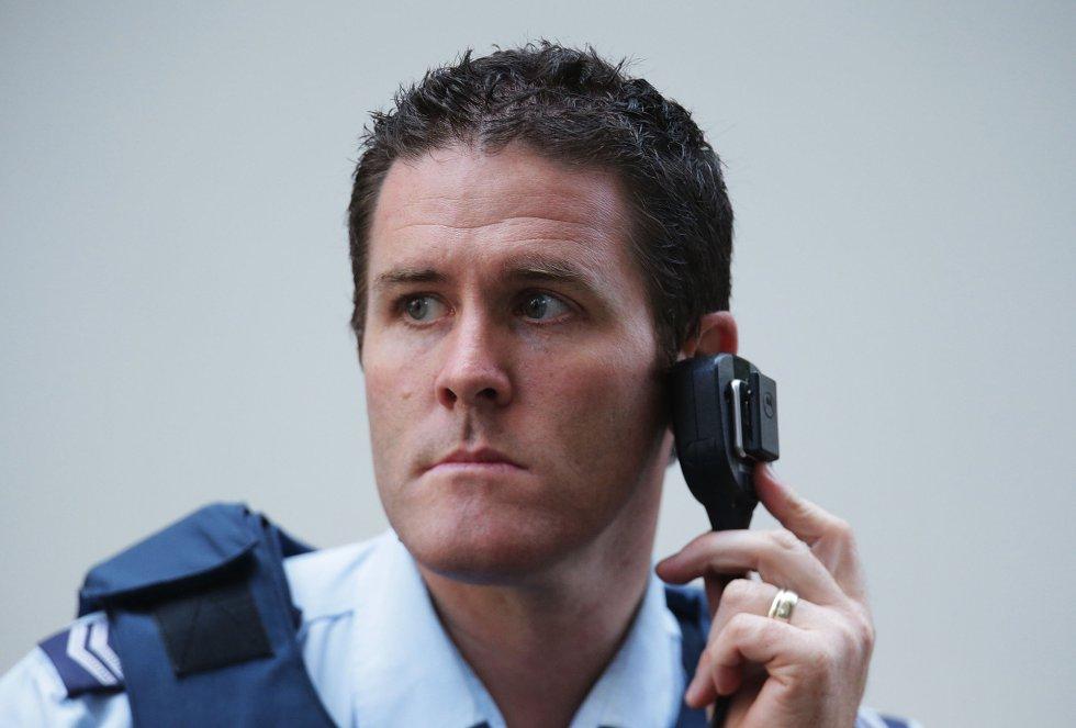 Un agente permanece atento a la emisora de la policía.
