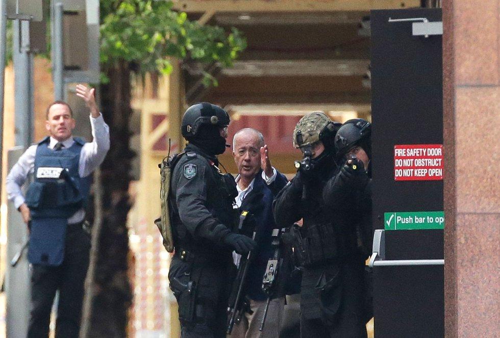 Uno de los rehenes que ha logrado escapar explica a los agentes la situación dentro del café.