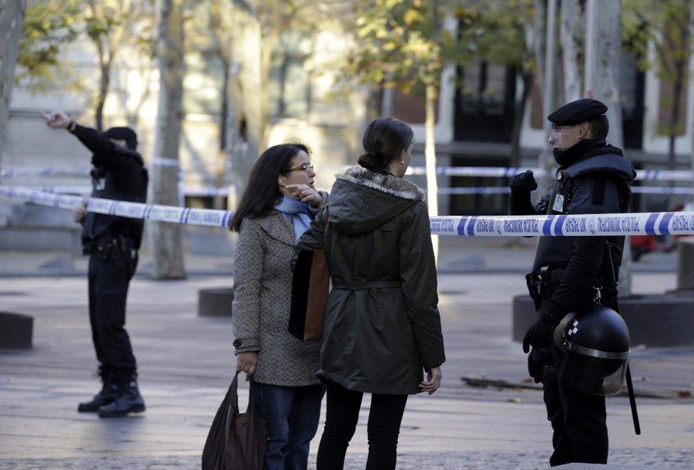 Un agente de Policía Nacional informa a dos ciudadanas en los alrededores de la calle Génova de Madrid.