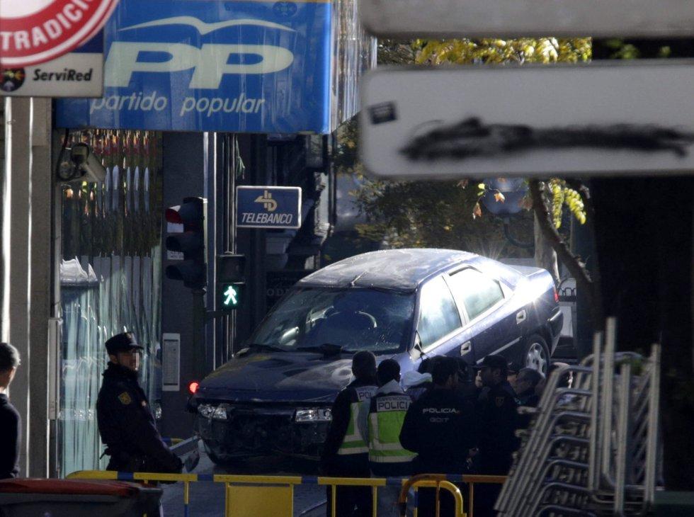 Una grúa retira el coche que permanecía en la sede del PP en la calle Génova de Madrid