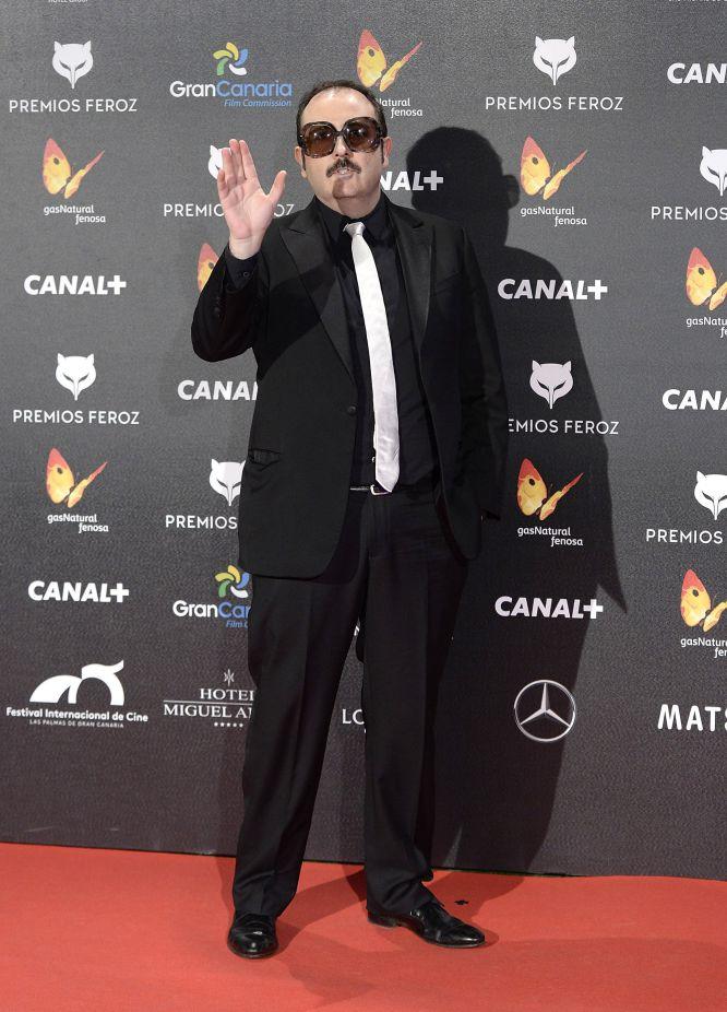 Carlos Areces, con gafas y corbata blanca sobre fondo negro, en los premios Feroz