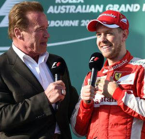 Hollywood actor Arnold Schwarzenegger (L) interviews Ferrari's German driver Sebastian Vettel (R) after the Formula One Australian Grand Prix in Melbourne on March 15, 2015. AFP PHOTO / William WEST --IMAGE RESTRICTED TO EDITORIAL USE - STRICTLY NO COMMERCIAL USE--