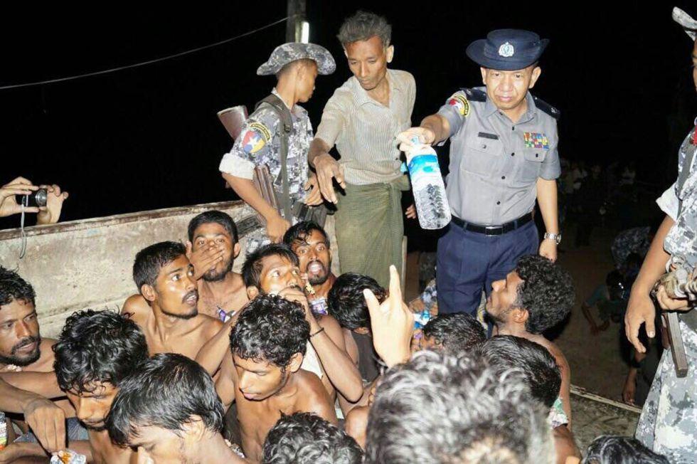 Un oficial de policía de Myanmar dando una botella de agua a los inmigrantes de un barco de pesca situado frente a la costa occidental de Rakhine.