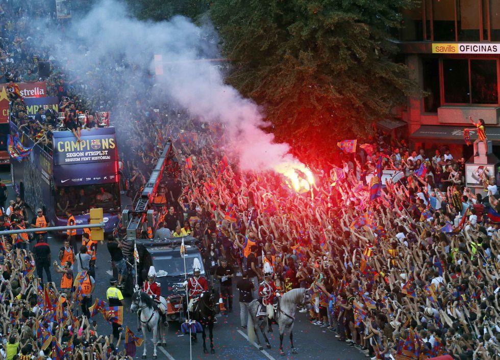 Los aficionados culés encienden bengalas al paso del autobús del Barça