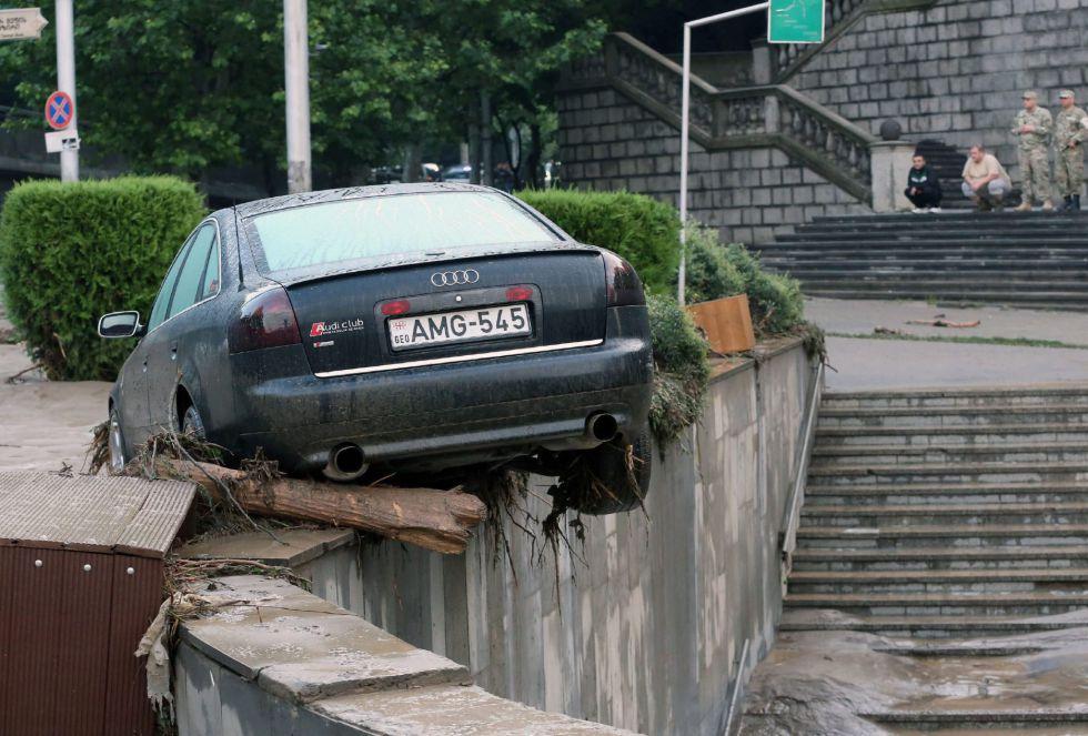 La imagen muestra un coche dañado durante las graves inundaciones en Tbilisi, que han causado múltiples destrozos.
