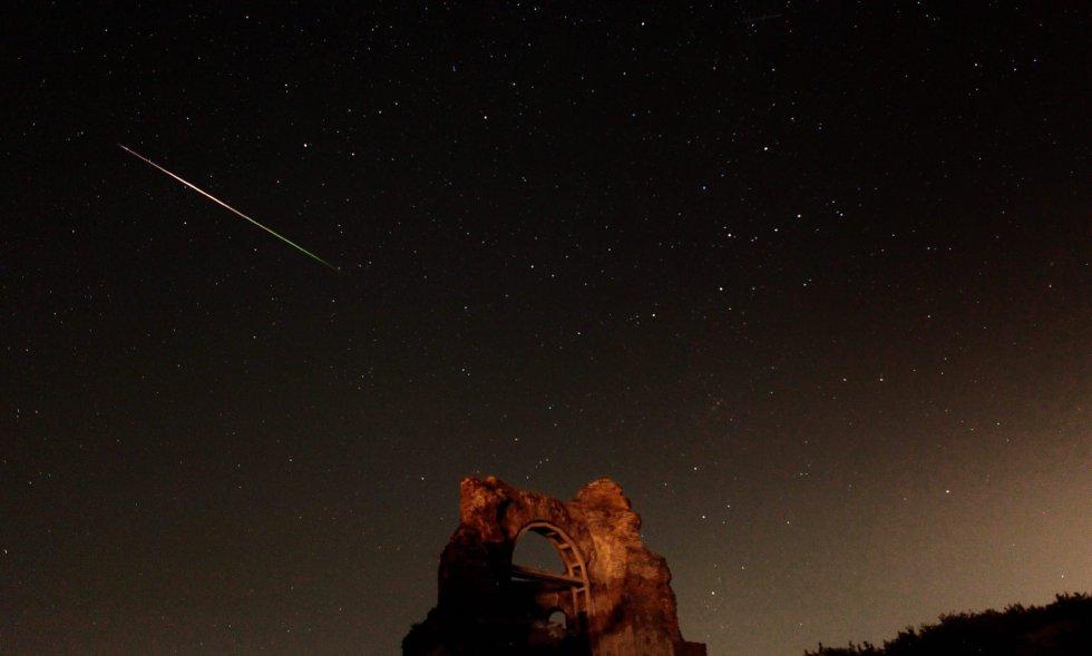"""Fotografía de larga exposición que muestra un meteoro mientras cruza en la noche, durante la basílica cristiana bizantina """"Iglesia Roja"""", que data del siglo IV y V, en Perushtitsa (Bulgaria)."""