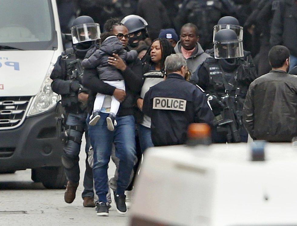 Fuerzas especiales evacúan a una familia del bloque de pisos donde la Policía ha llevado a cabo la operación antiterrorista.