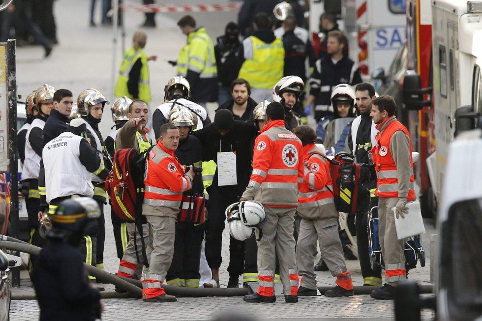 Personal médico asiste a un policía herido durante la operación en Saint-Denis.