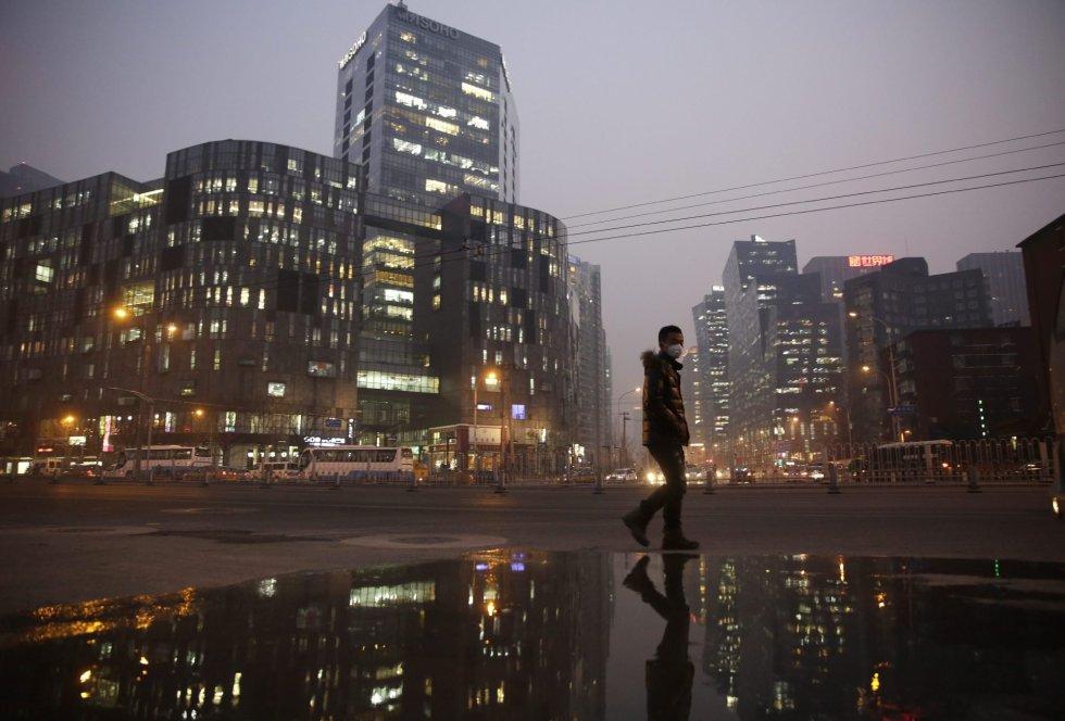 Un joven pasea con una mascarilla para protegerse de la contaminación en Pekín (China).