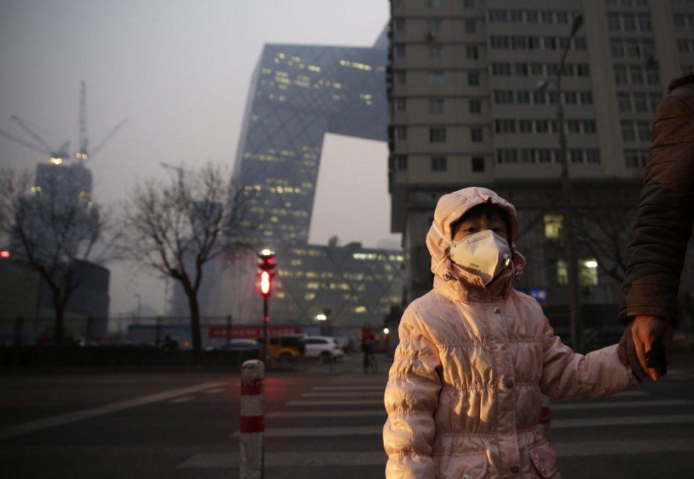 Una niña usa una mascarilla para protegerse de la contaminación ambiental en Pekín (China).