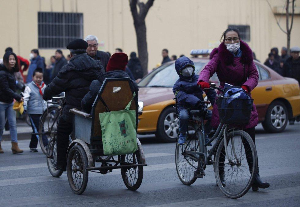 Una madre y su hijo usan mascarillas para protegerse de la contaminación ambiental en Pekín (China).