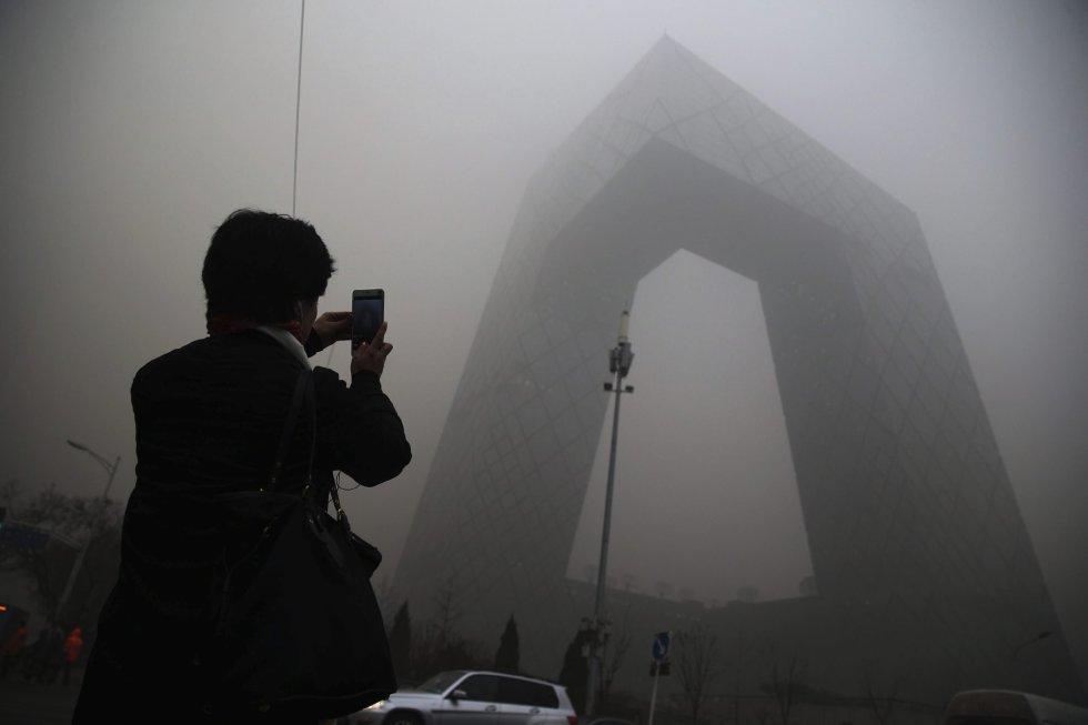 Una mujer realiza una foto en una calle de Pekín (China).