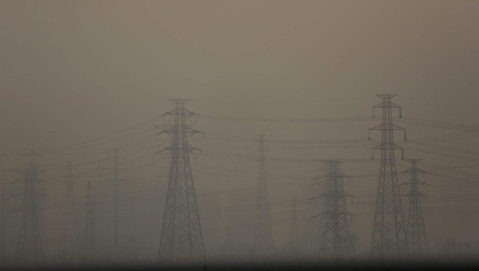 La bruma envuelve unas torres de electricidad en las afueras de Pekín (China).