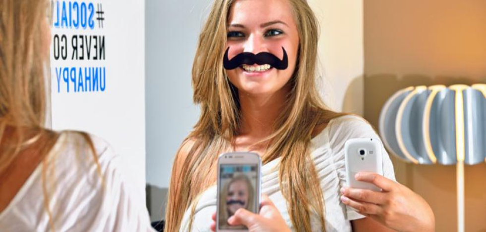 """Imagen de una joven haciéndose un selfie con un bigote que ilustra el espejo del baño de las habitaciones. La frase """"Do you like my new look?"""" está escrita encima. La red interna del hotel permite a los clientes comunicarse entre sí y facilita la personalización de servicios."""