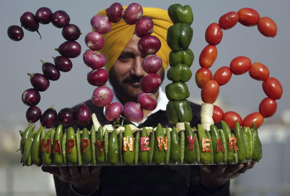 El artista indio Harwinder Singh Gill muestra su obra de arte hecha de verduras para celebrar el Año Nuevo en Amritsar (India).