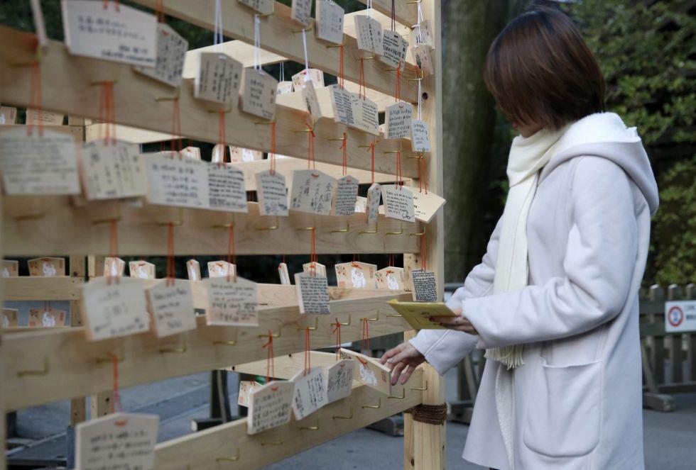 Una visitante cuelga una tablilla de madera donde ha escrito sus deseos para el 2016 en el templo Meiji de Tokio (Japón).