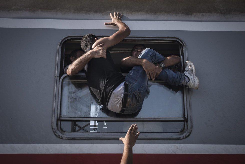 Fotografía de la serie ganadora de la categoría de noticias de actualidad de la 59 edición del World Press Photo, tomada por el fotógrafo ruso del New York Times Sergey Ponomarev. La fotografía muestra a un inmigrante luchando por subir a un tren, en Zagreb (Croacia).