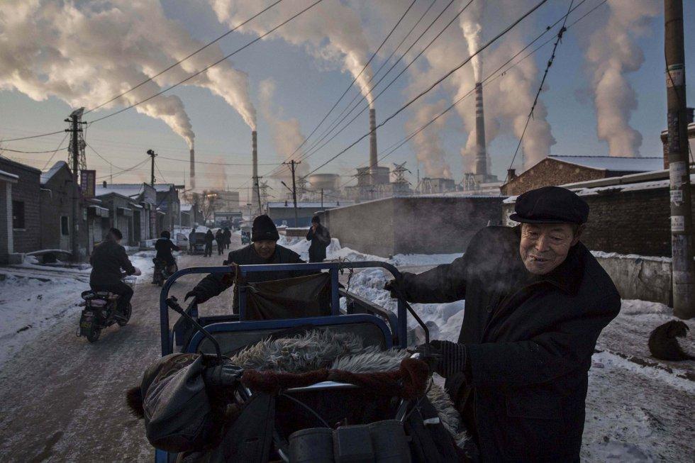Primer premio en la categoría 'Vida diaria'. Hombres chinos tiran de un vehículo de tres ruedas en una zona próxima a una planta térmica de carbón en Shanxi, China, el 26 de noviembre de 2015. China depende en gran medida de la quema de carbón para producir energía, lo que le ha convertido en la fuente de casi un tercio del dióxido de carbono total del mundo (una de las principales causas del calentamiento global).
