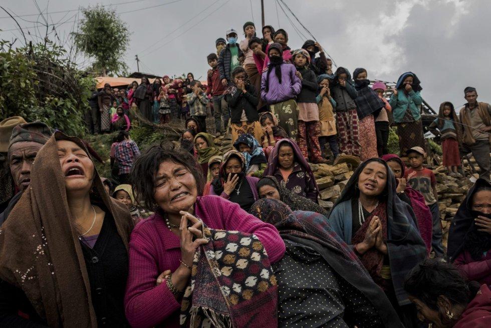 Fotografía de la serie ganadora del tercer premio en 'Historias' de la categoría individual de noticias de actualidad de la 59 edición del World Press Photo, tomada por el fotógrafo australiano del New York Times Daniel Berehulak. La fotografía muestra varias mujeres llorando mientras el cuerpo sin vida de la pequeña Rejina Gurung de tres años es recuperado de entre los escombros, en Gumda (Nepal) el 8 de mayo de 2015.