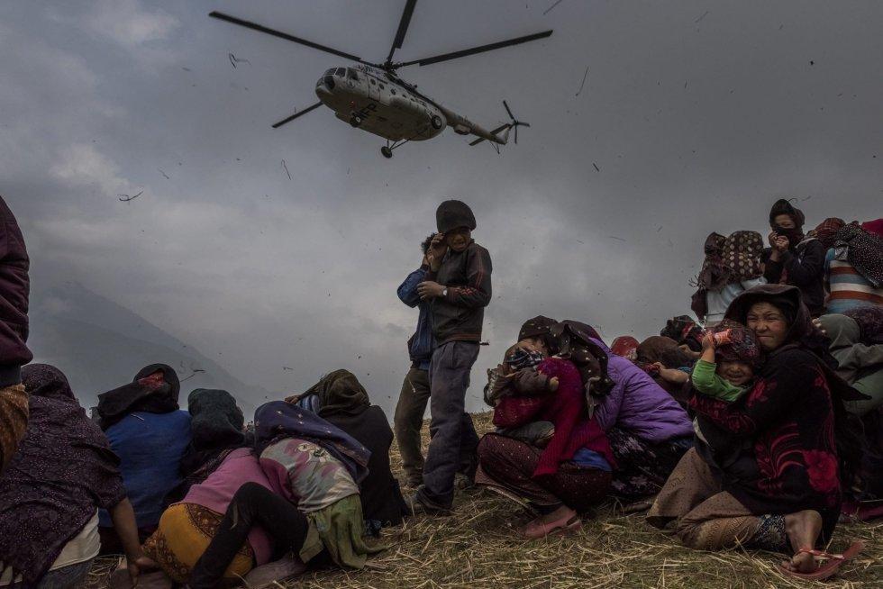 """Fotografía de la serie ganadora en """"Historias"""" del tercer premio de la categoría individual de noticias de actualidad de la 59 edición del World Press Photo, tomada por el fotógrafo australiano del New York Times Daniel Berehulak. La fotografía muestra a varias personas que aguardan la llegada del helicóptero con la ayuda sanitaria en Gumda (Nepal) el 9 de mayo de 2015, tras el terrible terremoto que se cobró más de 8.000 vidas."""