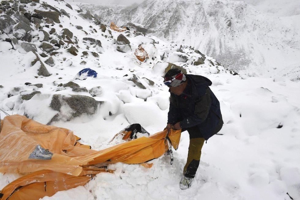 """Fotografía de la serie ganadora del segundo premio en """"Historias"""" de la categoría de deportes de la 59 edición del World Press Photo, tomada por el fotógrafo colombiano Roberto Schmidt. La fotografía muestra a un sherpa buscando supervivientes tras el desprendimiento de roca, hielo y nieve que acabó con la vida de más de 22 personas en el Everest, en el Himalaya, el 25 de abril 2015."""
