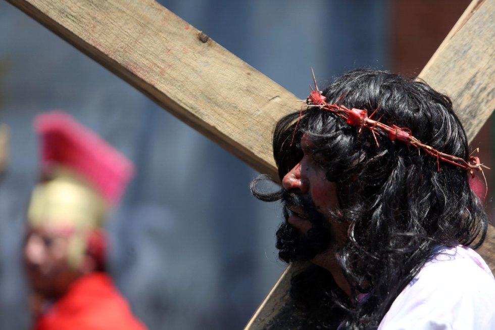 Un hombre caracterizado como Jesús carga una cruz de madera durante la representación de la pasión de cristo en un Vía Crucis en vivo en el municipio de Villa Nueva (Guatemala).