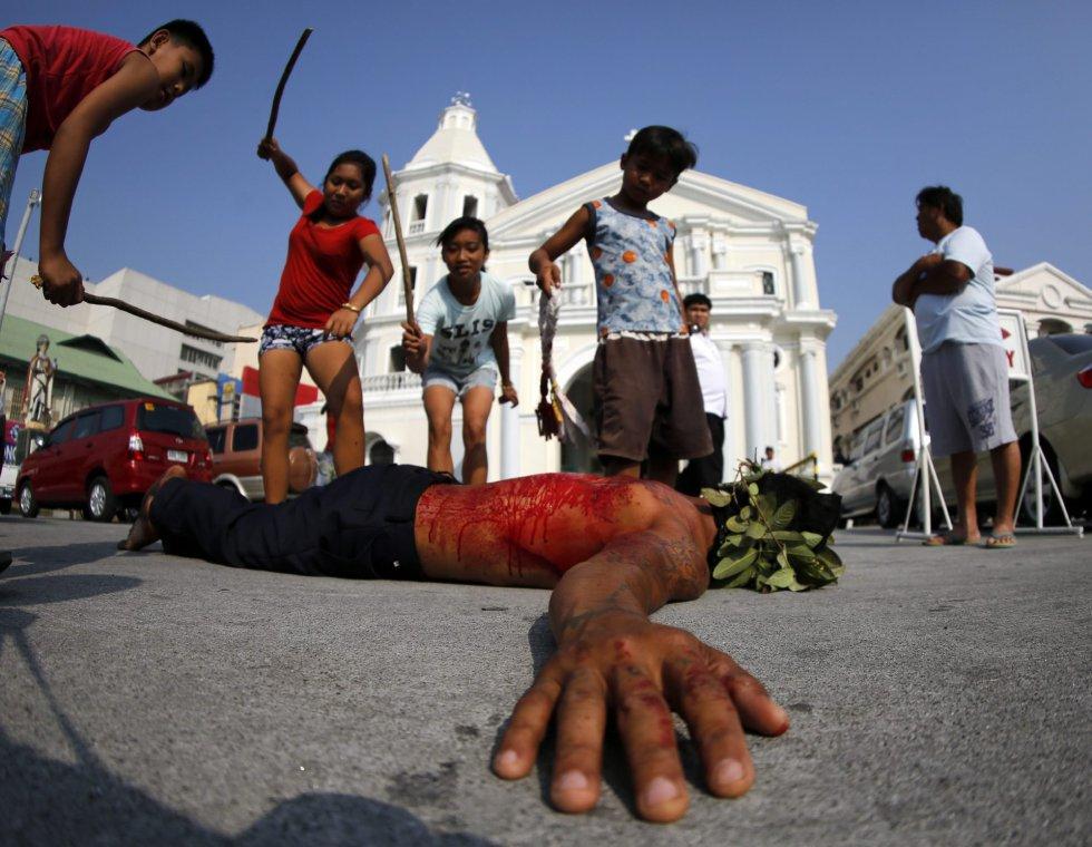 Niños pegan a un penitente flagelado en San Pedro Cutud en San Fernando al norte de Manila (Filipinas).