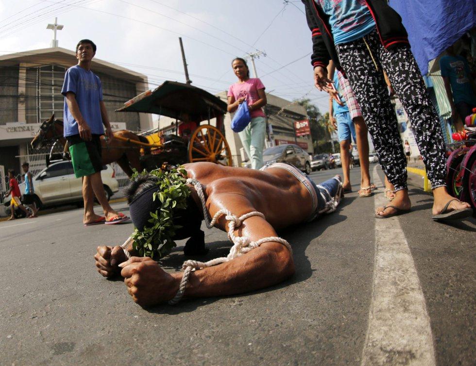 Un penitente se arrastra por el suelo para llegar a la iglesia en San Pedro Cutud en San Fernando al norte de Manila (Filipinas).