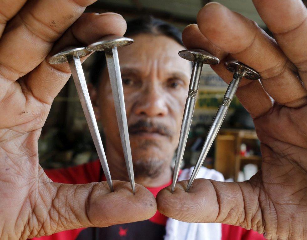 El penitente Ruben Enaje muestra los cuatro clavos que serán utilizados para crucificarle otra vez, como cada año desde hace 30, en San Pedro Cutud en San Fernando al norte de Manila (Filipinas).
