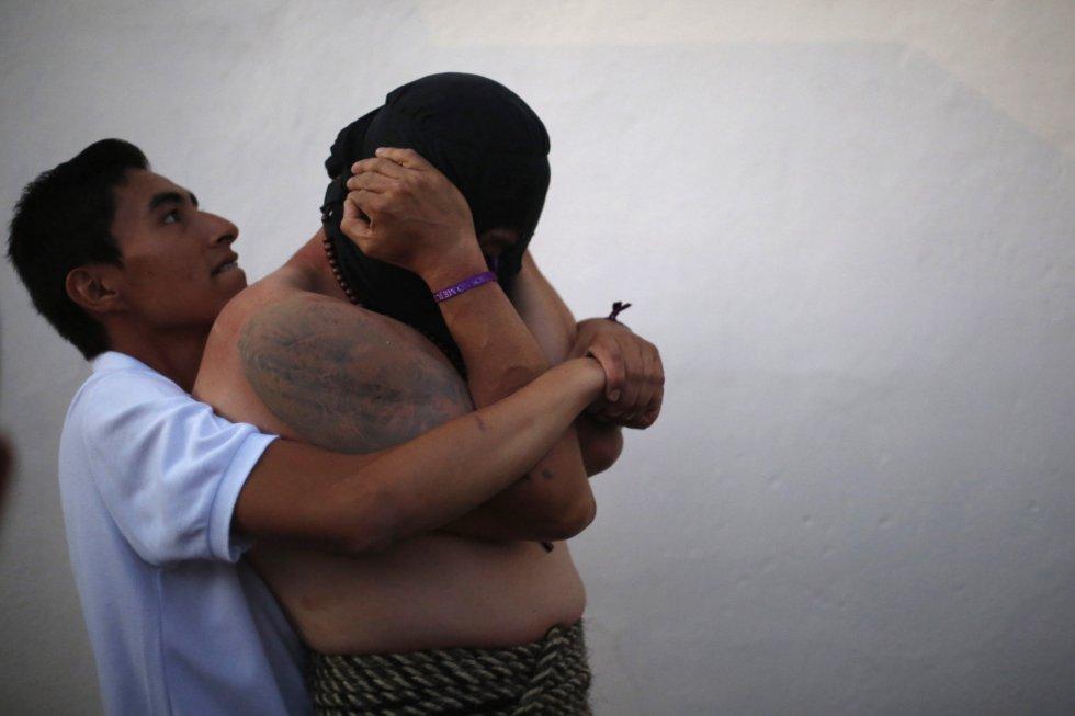 Un hombre ayuda a otro a preparar los músculos antes de una procesión en Taxco, en el estado mexicano de Guerrero.