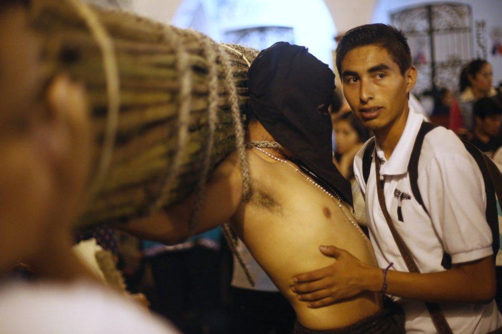 Un hombre ayuda a un penitente mientras éste lleva una cruz a su espalda, en Taxco (México).