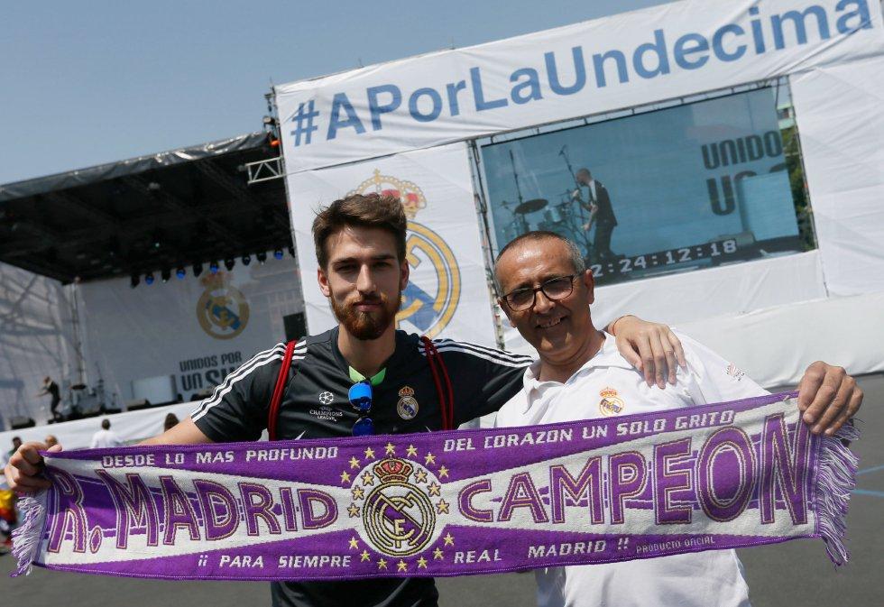Dos aficionados madridistas, con una bufanda de su equipo, en la 'fan zone' del Madrid en Milán
