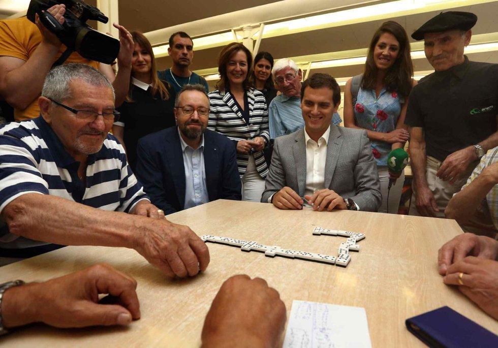 El candidato de Ciudadanos a presidente, Albert Rivera, juega una partida de dominó durante su visita al Casal de Gent Gran Can Saladrigas en Barcelona.