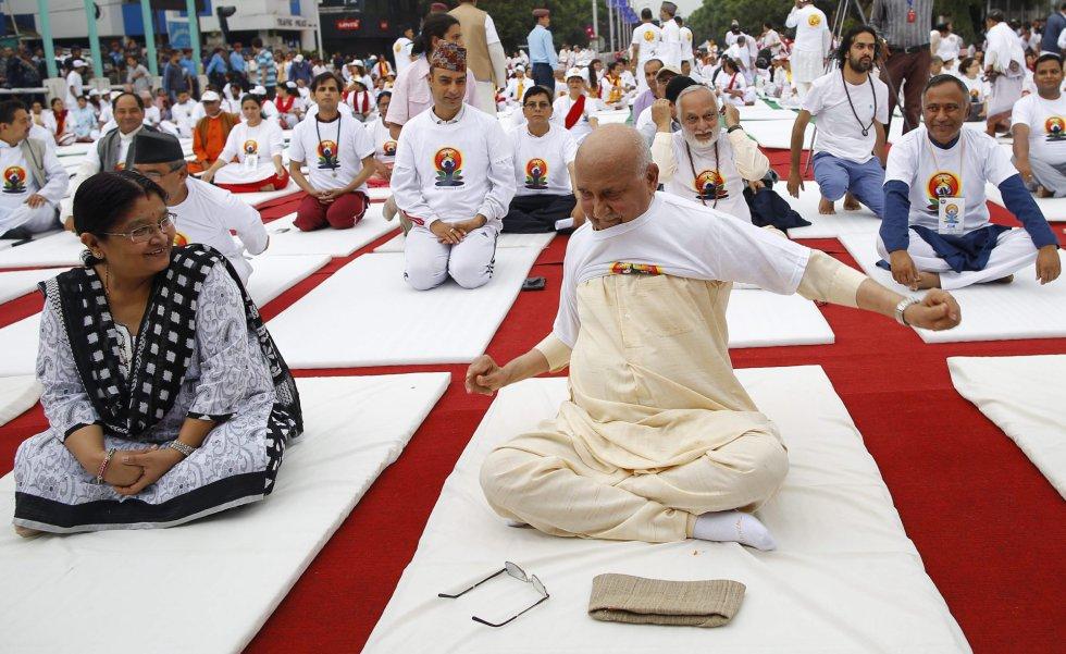 El primer ministro nepalí, Khadga Prasad Sharma Oli se pone una camiseta para practicar yoga junto a una multitud en Katmandú (Nepal) durante la celebración del Día Internacional del Yoga.