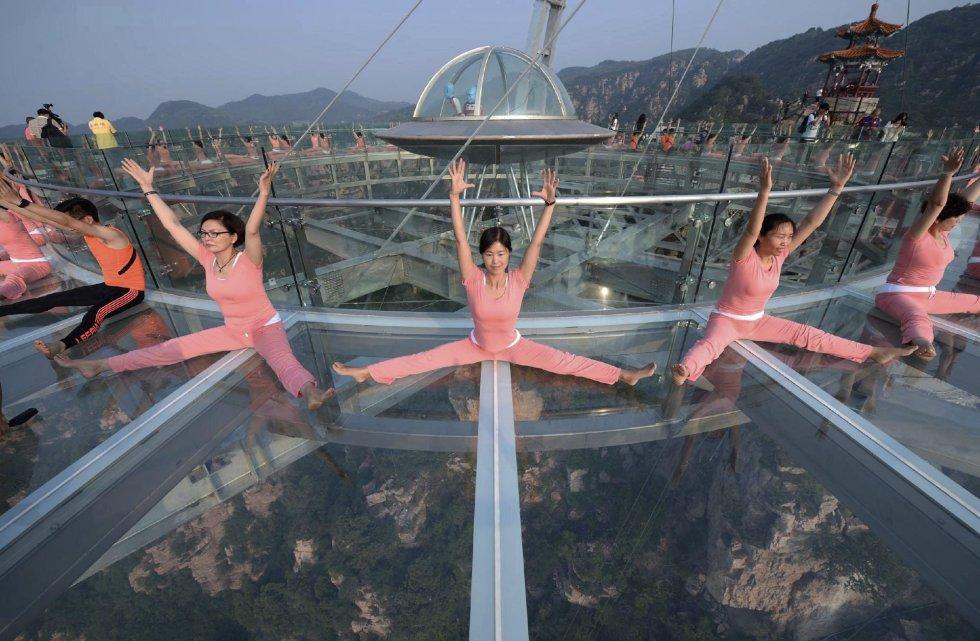 Cientos de practicantes de yoga mientras participan su disciplina favorita en el mayor mirador del mundo de cristal y titanio con forma de platillo en Pekín (China).