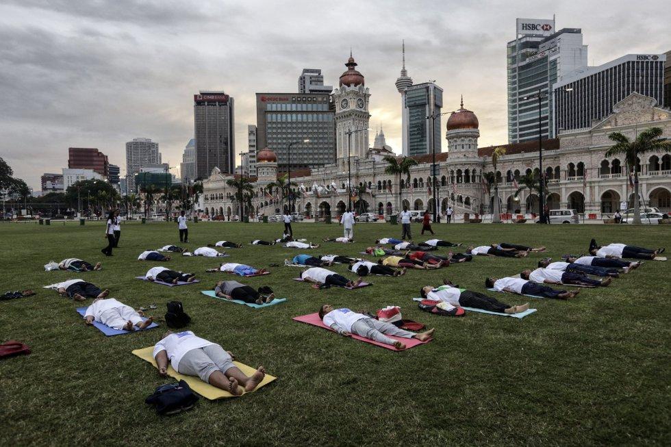 Un grupo de personas participa en el Día Internacional de Yoga en Kuala Lumpur (Malasia).