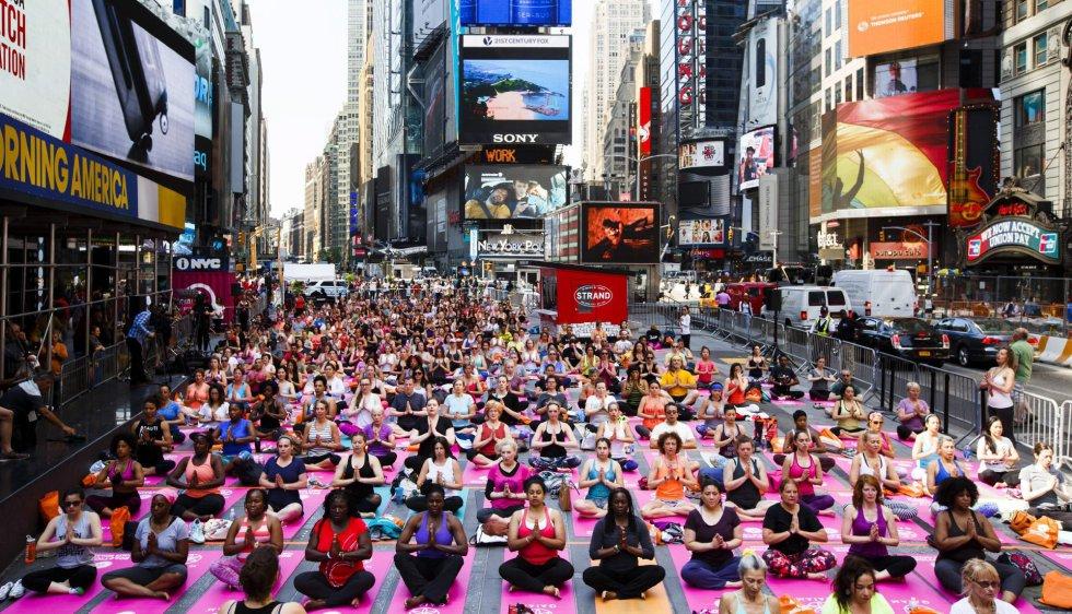 """Cientos de personas participan en una clase de yoga en Times Square con motivo de la decimocuarta edición anual del evento """"Solstice in Times Square: Mind Over Madness Yoga"""" que marca el inicio del solsticio de verano en Nueva York, Estados Unidos, un día antes del Día Internacional del Yoga."""