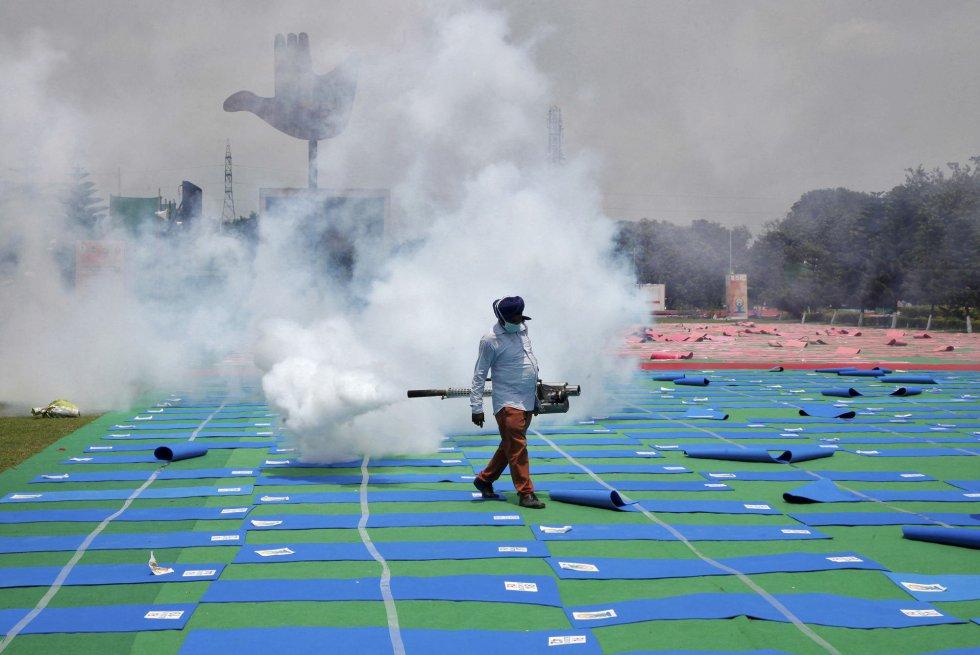 Un trabajador fumiga un campo de Yoga en la vispera del Día Internacional del Yoga. Chandigarh, India.