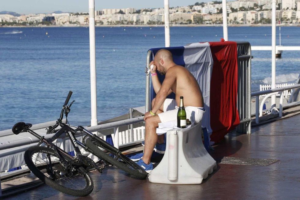 Un hombre llora sentado al lado de la bandera francesa