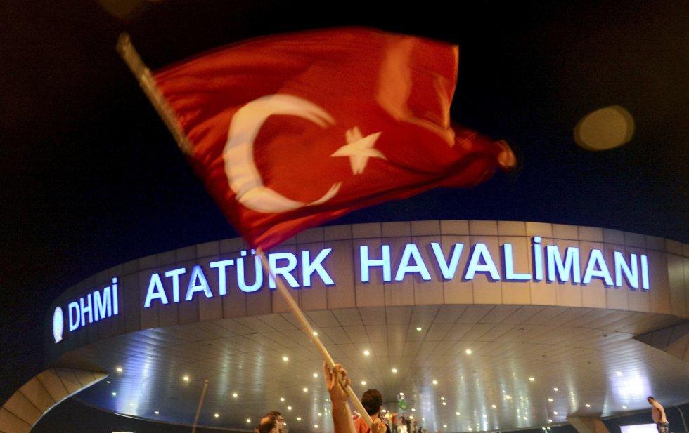 Un hombre porta una bandera turca frente a la fachada del aeropuerto de Ataturk