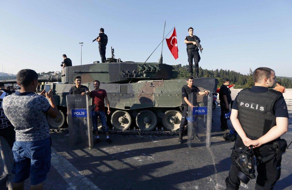 Los ciudadanos posan con la policía frente a uno de los tanques de los soldados golpistas ya detenidos