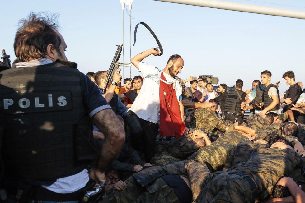 Un hombre usa su cinturon para golpear a los militares detenidos durante la noche por el intento de un golpe de Estado en Turquía