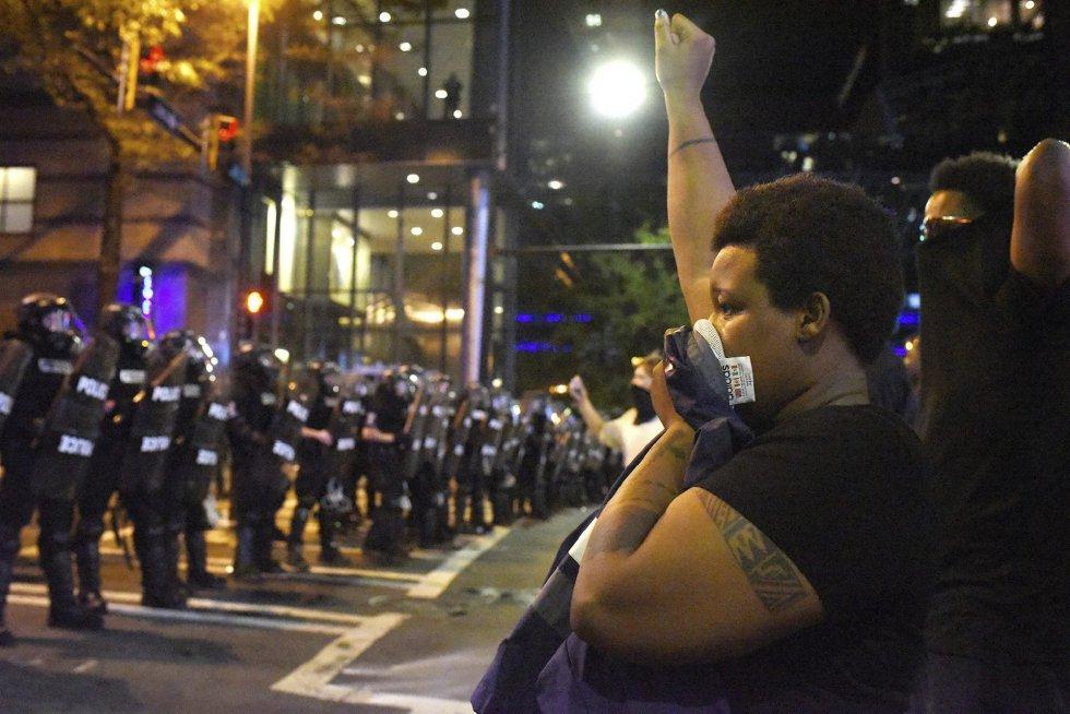 Manifestantes se encaran a policías antidisturbios con los brazos en alto durante unos disturbios en Charlotte en Carolina del Norte (Estados Unidos).