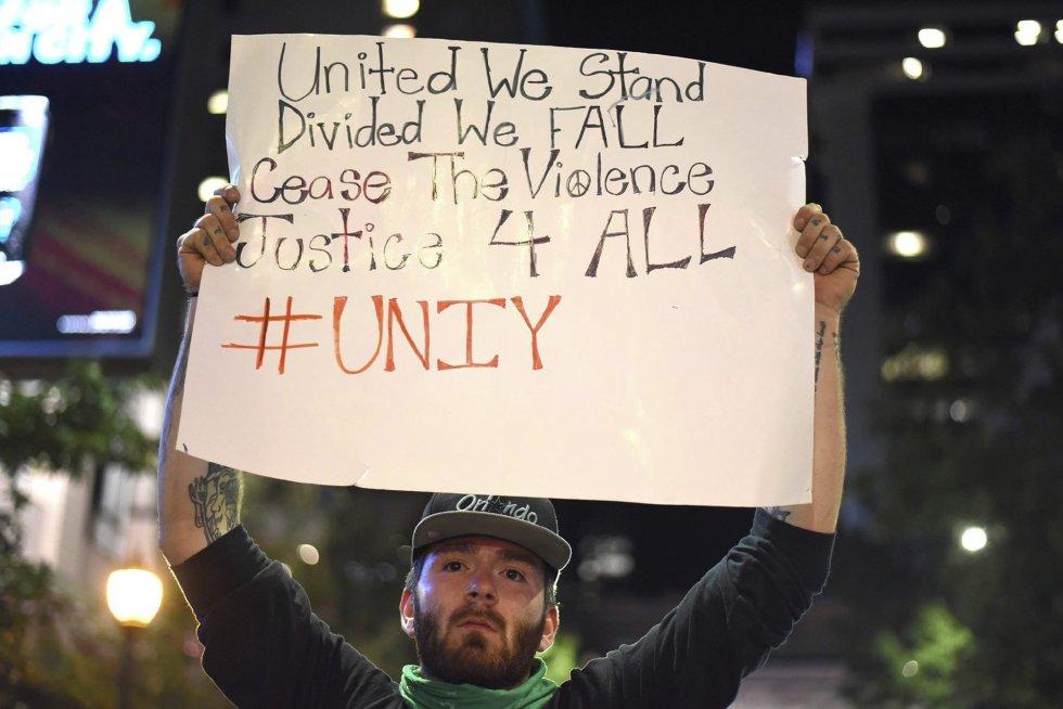 """Un manifestante sostiene una pancarta en la que se puede leer """"Unidos permanecemos en pie, divididos caemos, parad la violencia justicia para todos"""" durante unos disturbios en Charlotte en Carolina del Norte (Estados Unidos)."""