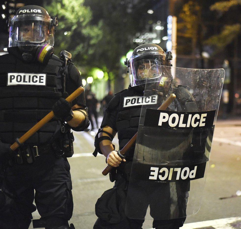 Policías antidisturbios permanecen en guardia durante unos disturbios en Charlotte en Carolina del Norte (Estados Unidos).